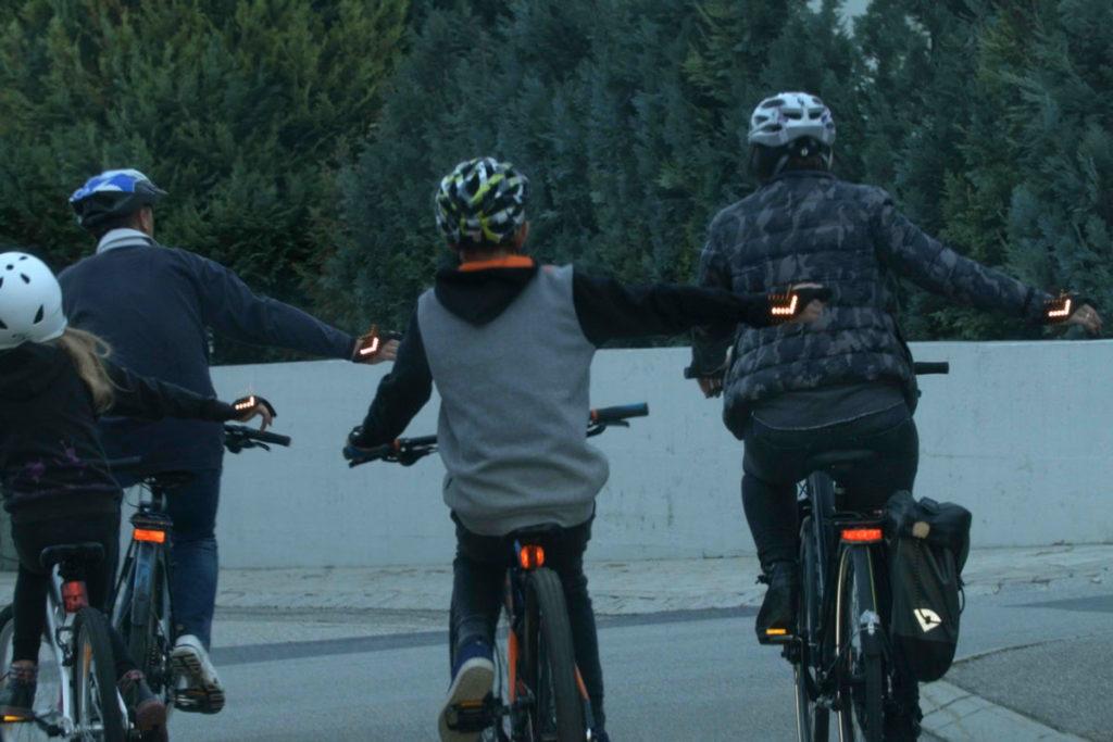 Familie fährt mit Fahrrädern in der Dämmerung und möchte mit dem flash2bsafe Handschuh abbiegen.