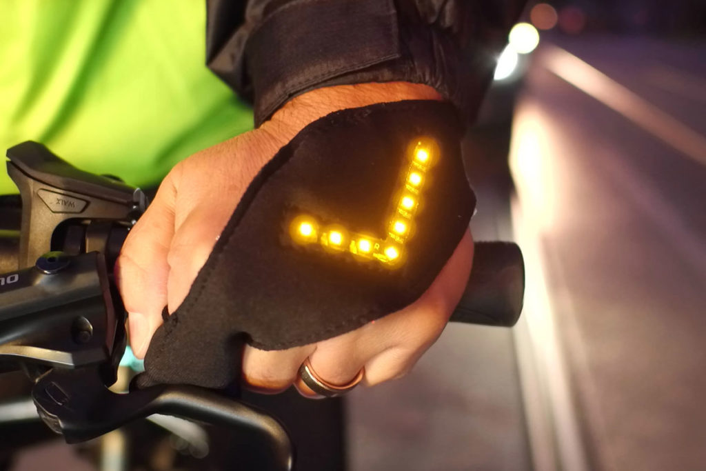 Hand auf einem Fahrradlenker trägt einen leuchtenden flash2bsafe Handschuh.