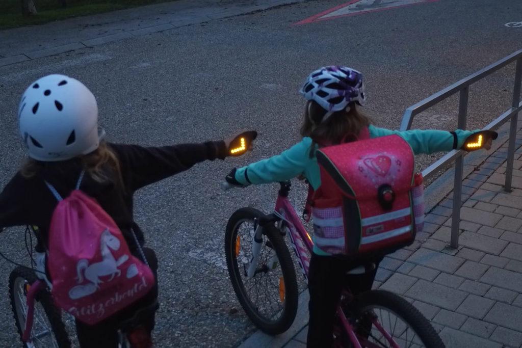 Zwei Kinder stehen mit Fahrrädern an einer Ausfahrt und strecken ihre rechte Hand mit dem flash2bsafe Handschuh zum abbiegen aus.